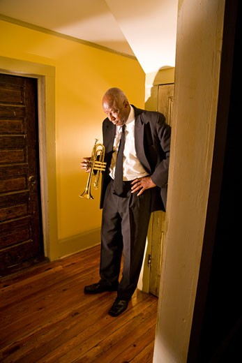 Stock Photo: 1785-14728 Senior African American jazz musician standing in hallway with trumpet