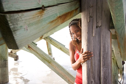 Young Jamaican woman looking from behind beach pier : Stock Photo