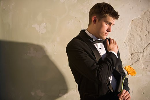 Portrait of young man in tuxedo holding a flower : Stock Photo