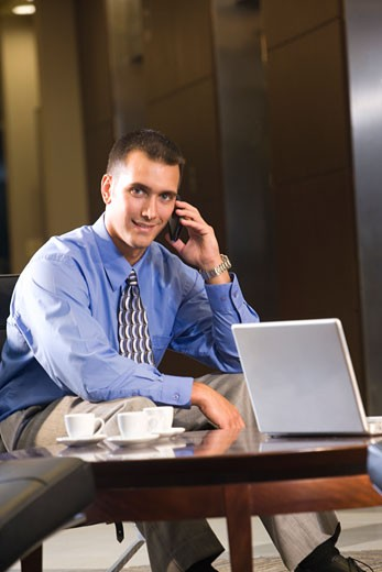 Portrait of businessman sitting in lobby using mobile phone : Stock Photo