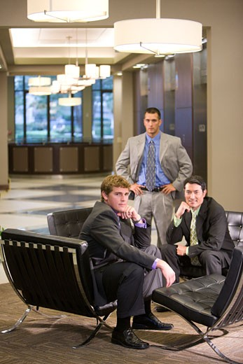 Portrait of multi-racial businessmen sitting in modern lobby : Stock Photo