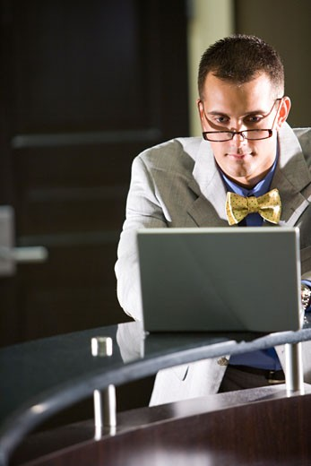 Businessman wearing bowtie and eyeglasses using laptop : Stock Photo