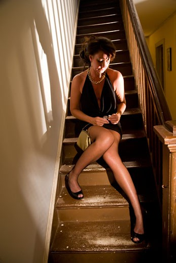 Hooker lighting cigarette while sitting on stairs in house : Stock Photo