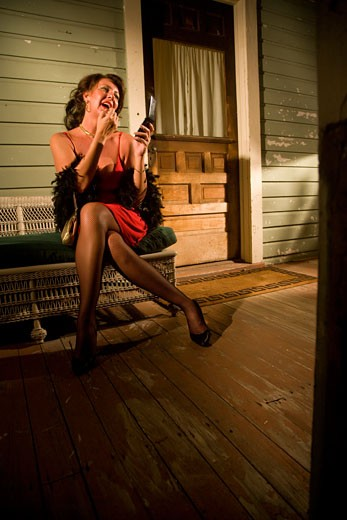 Sexy middle-aged woman applying lipstick on porch of house : Stock Photo