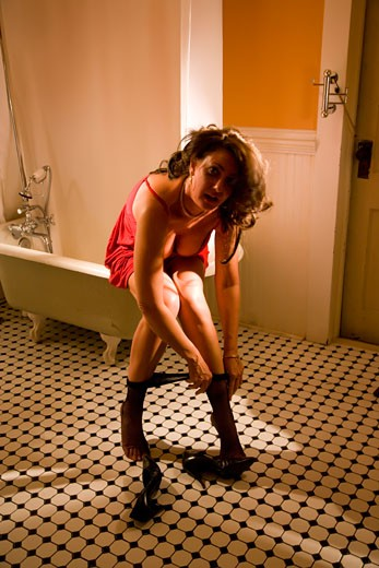 Portrait of sexy hooker in bathroom pulling up her stockings : Stock Photo