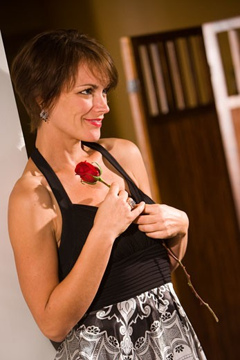 Smiling mid-adult woman holding red rose : Stock Photo