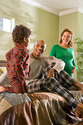 Pregnant African American woman standing in bedroom with family : Stock Photo