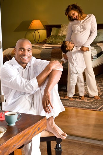 African-American man sitting at table, family in background : Stock Photo