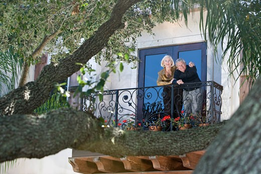 Stock Photo: 1785-16909 Portrait of senior couple standing on balcony of luxury house