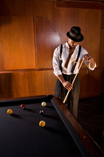 African American man holding pool stick in 1920s billiard bar : Stock Photo