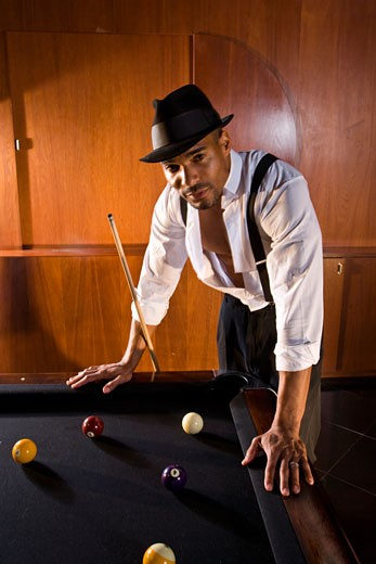 Stock Photo: 1785-17065 African American man leaning over billiards table in 1920s bar