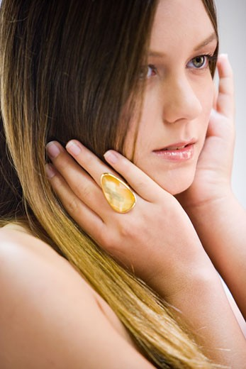 Stock Photo: 1785-17354 Portrait of young woman wearing jeweled ring, studio shot