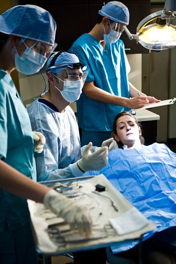 Portrait of dentist and assistants working on patient : Stock Photo