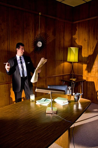 Vintage portrait of businessman relaxing with cigarette in boardroom : Stock Photo