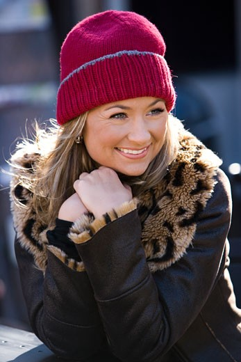 Young woman in warm clothing sitting at outdoor table : Stock Photo