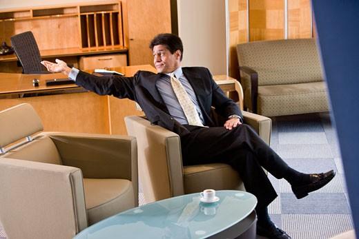 Stock Photo: 1785-17919 Mature Hispanic man sitting in lounge area beckoning