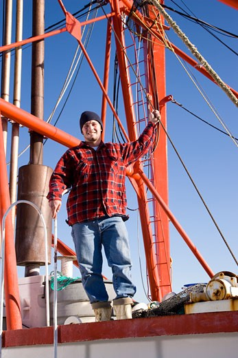 Young fisherman in plaid shirt standing on fishing boat : Stock Photo