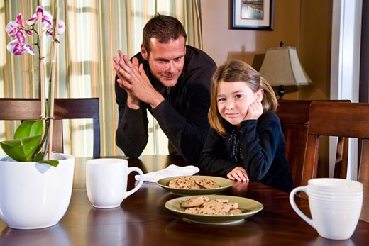 Father and daughter sitting at dining room table with cookies : Stock Photo