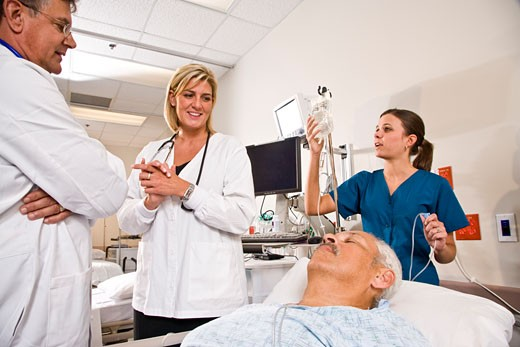 Doctors and nurse in hospital recovery room with patient : Stock Photo