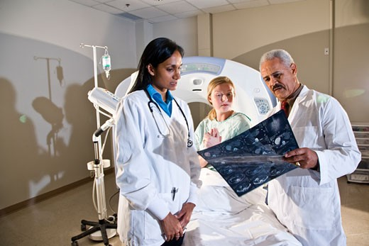 Radiologists and patient looking at results of CAT scan : Stock Photo
