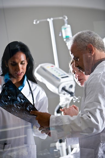 Radiologists looking at test results with patient near CT scanner : Stock Photo