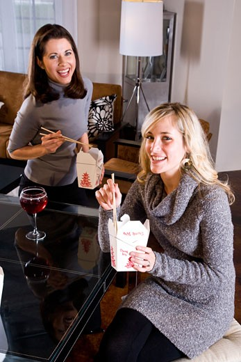 Young women eating Chinese take-out in living room : Stock Photo