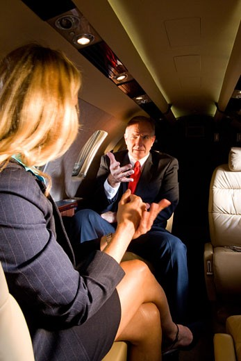 Businessman and businesswoman sitting on small private jet : Stock Photo
