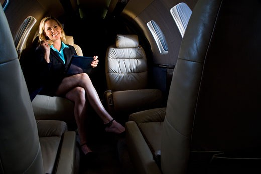 Businesswoman sitting in small private jet plane : Stock Photo