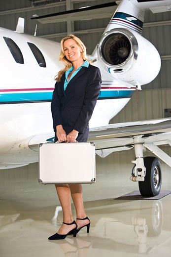 Stock Photo: 1785-19192 Businesswoman with briefcase standing next to corporate jet