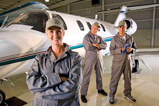 Three airplane mechanics standing next to small planes in hangar : Stock Photo