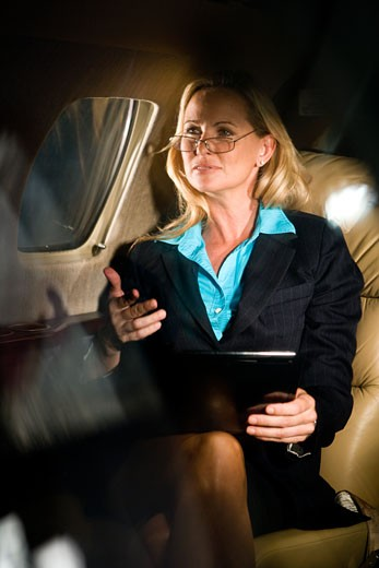Stock Photo: 1785-19215 Businesswoman traveling in corporate jet