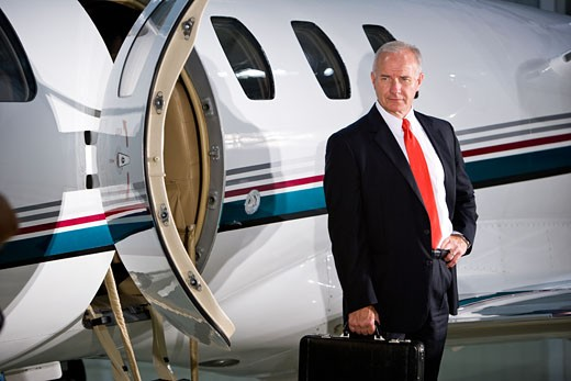 Middle-aged businessman leaving private jet plane : Stock Photo