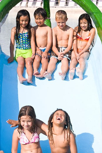 Multi-ethnic children on slide at water park in summer : Stock Photo