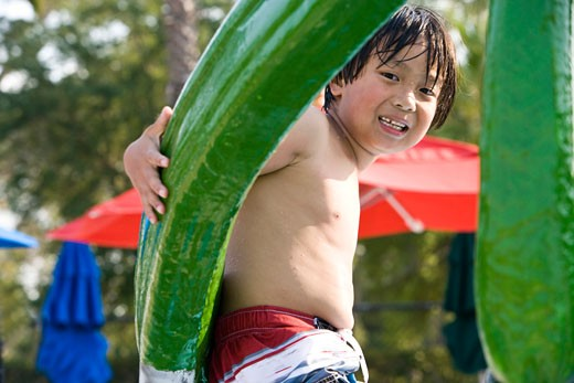 Young Asian boy playing at water park in summer : Stock Photo