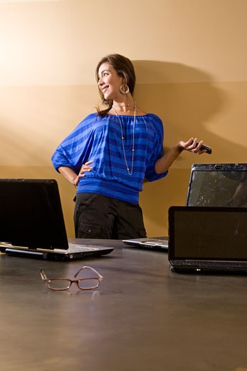 Stock Photo: 1785-19442 Hispanic woman in blue shirt standing against wall