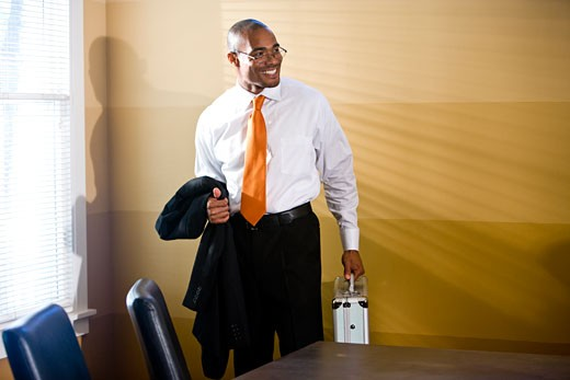 Stock Photo: 1785-19515 Businessman standing in office holding briefcase and jacket