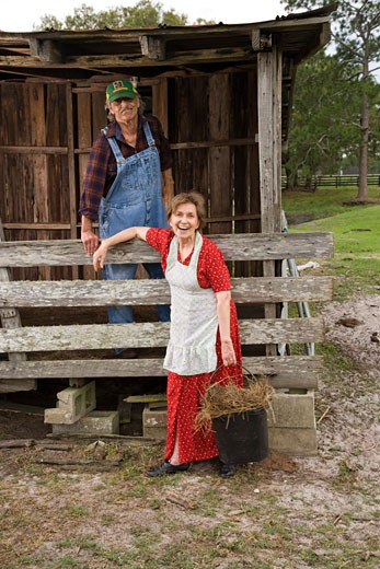 Stock Photo: 1785-19550 Senior couple on farm working near barn