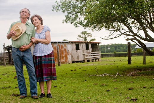 Senior couple standing together outside old farmhouse : Stock Photo