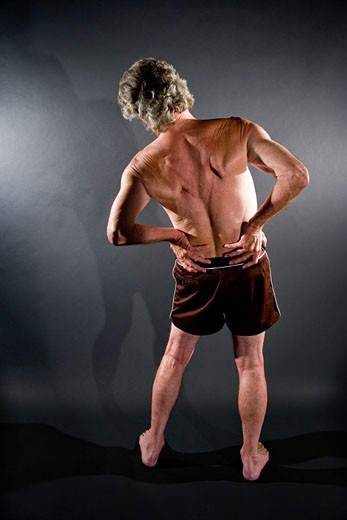 Rear view of senior man with hands on lower back, studio shot : Stock Photo