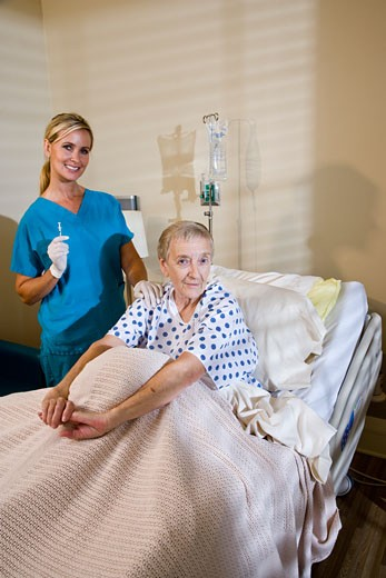 Stock Photo: 1785-19750 Elderly woman in hospital bed with nurse holding syringe