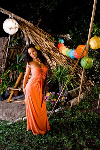Stock Photo: 1785-19816 Young Hispanic woman in orange dress standing in tropical garden on island