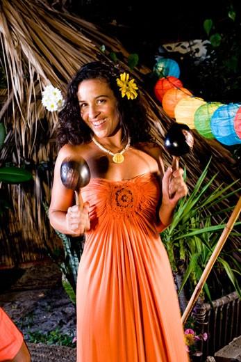 Young Hispanic woman in orange dress shaking maracas on tropical island : Stock Photo
