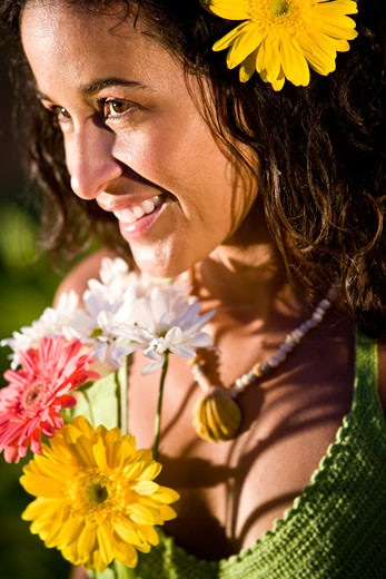 Close-up portrait of young Hispanic woman holding flowers on tropical island : Stock Photo