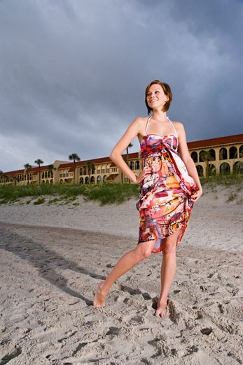 Young woman in colorful sundress standing on beach in front of resort : Stock Photo