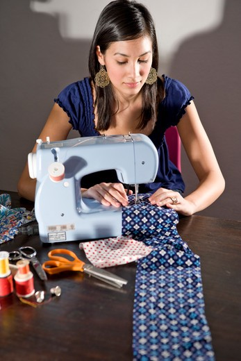 Young woman stitching fabric with sewing machine : Stock Photo