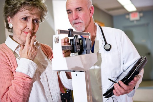 Stock Photo: 1785-39130 Doctor weighing senior woman on scale