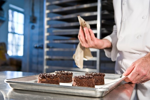 Stock Photo: 1785-39280 Cropped view of pastry chef decorating chocolate dessert pastries
