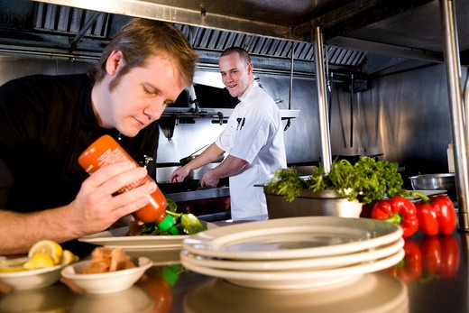 Stock Photo: 1785-39320 Sous chef in commercial kitchen preparing dishes