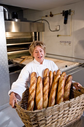 Mature woman carrying baked loaves of bread from commercial baker oven : Stock Photo