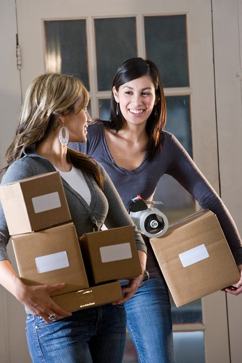 Two young women carrying cardboard boxes down hallway : Stock Photo